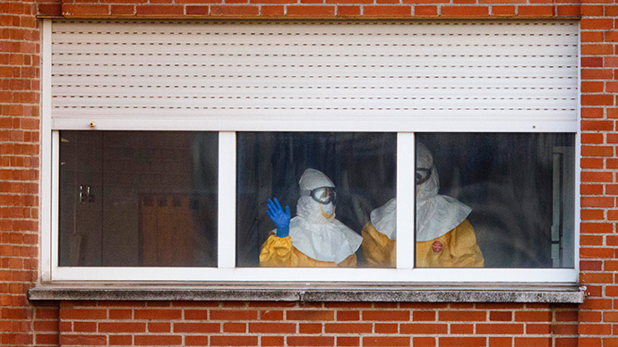 Health workers in protective suits stand near a window at an isolation ward on the sixth floor of Madrid's Carlos III Hospital October 12, 2014 (Reuters / Paul Hanna)
