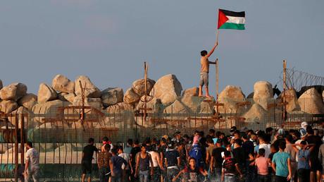 Un manifestant brandit un drapeau palestinien en franchissant la barrière israélienne lors d'une manifestation à la frontière maritime avec Israël, dans le nord de la bande de Gaza, le 8 octobre 2018.