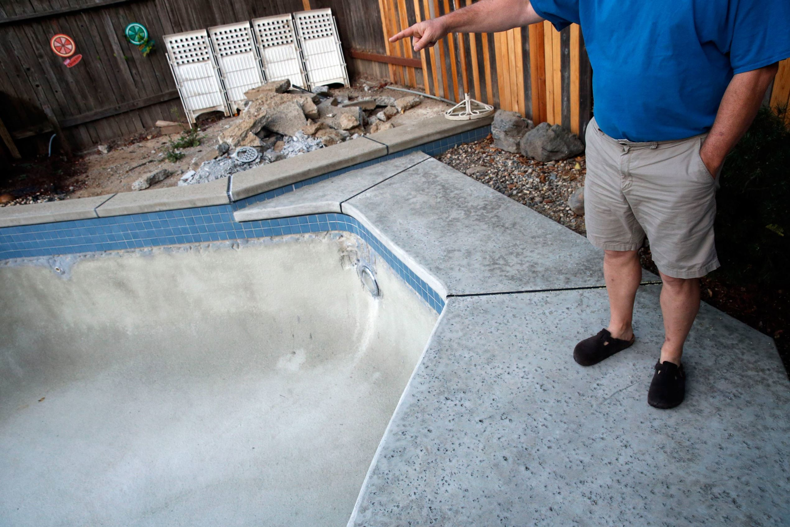 A homeowner points toward his drained swimming pool that cannot be refilled this summer due to water restrictions in Sacramento, California.