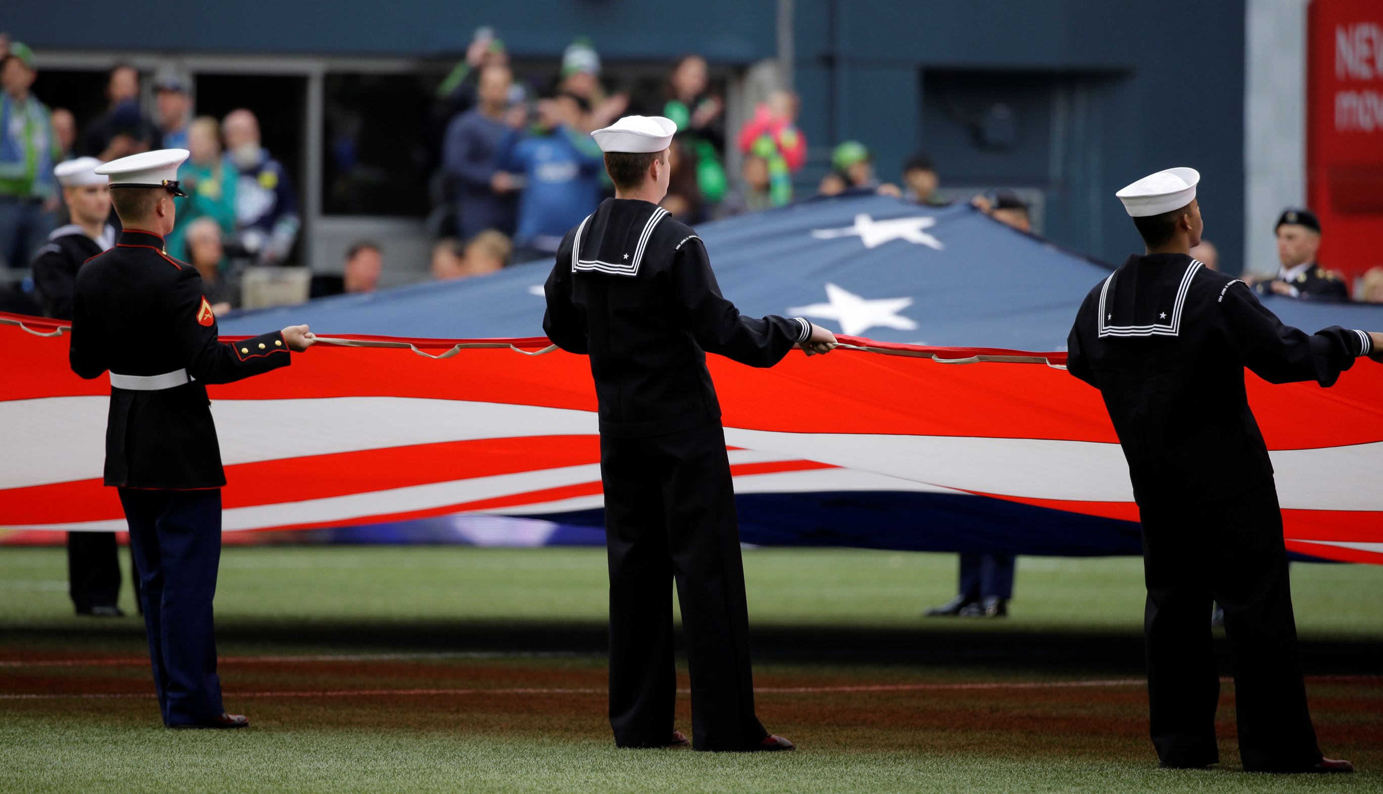 Members of the military hold a giant U.S. flag before an MLS soccer match between the Seattle Sounders and Sporting Kansas City, in Seattle, May 23, 2015.