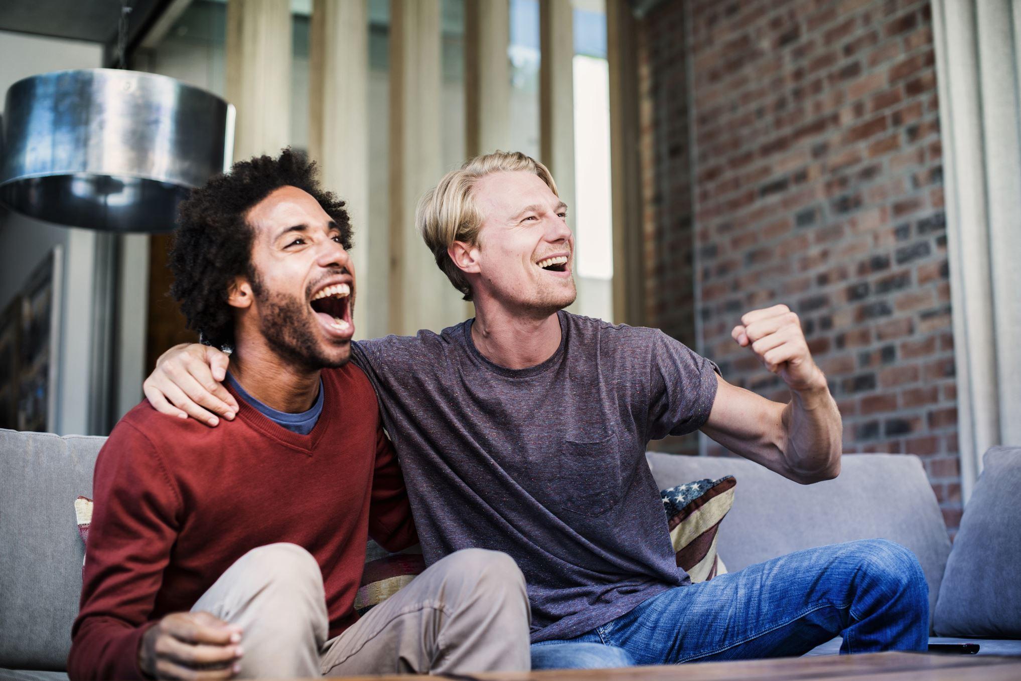 Men friends cheering sports team on tv