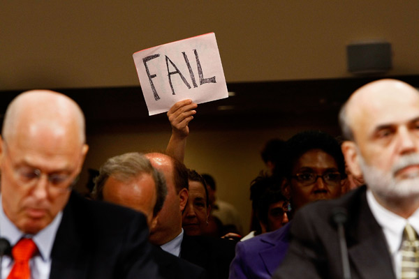 A demonstrator holds a fail sign at a Senate hearing on the financial crisis