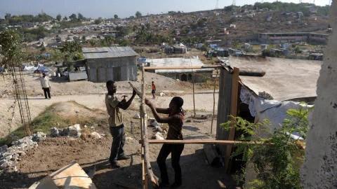 Un homme et sa soeur construisent un abri dans le quartier Caguas de Port-au-Prince.