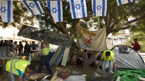 Des inspecteurs municipaux accompagnés par les forces de police démantèlent des structures de bois bâties par les manifestants dans la ville de Holon, au sud de Tel-Aviv.