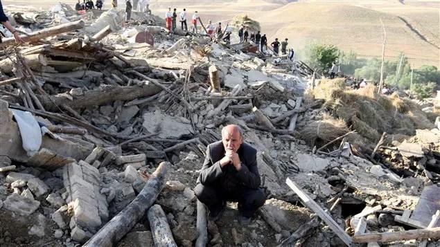 Un Iranien se tient au milieu de sa maison dévastée par le séisme du 11 août, près de Varzeghan, dans le nord-ouest du pays.