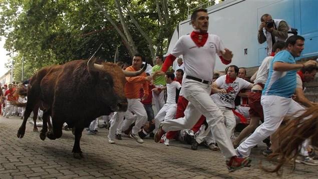 Course de taureaux dans les rues de Pampelune, en Espagne, le 12 juillet