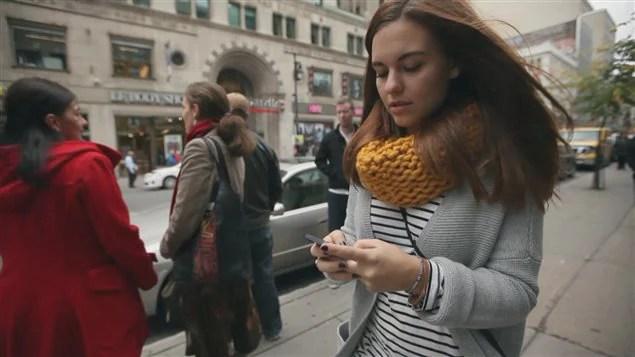 Une jeune femme texte en marchant