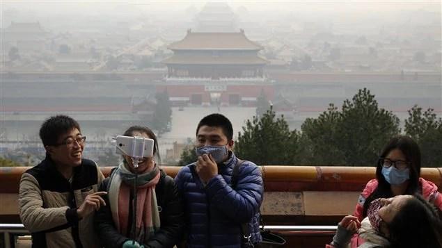 Des touristes en Chine portent un masque pour se protèger contre la pollution.