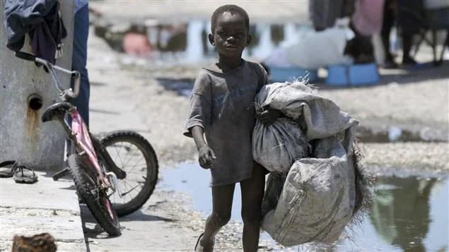 Un enfant haïtien transporte des sacs à Port-au-Prince