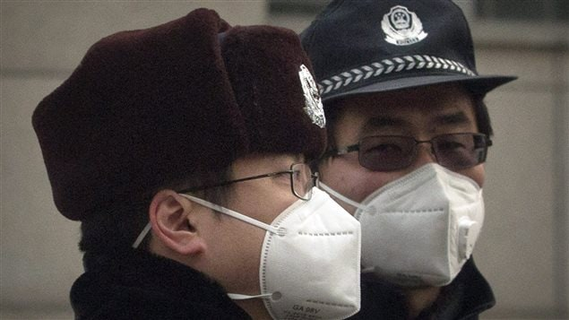 Chinese policemen wear pollution masks as they stand guard near the Beijing No. 2 People's Intermediate Court where human rights lawyer Pu Zhiqiang was sentenced in Beijing, China, Tuesday, Dec. 22, 2015.