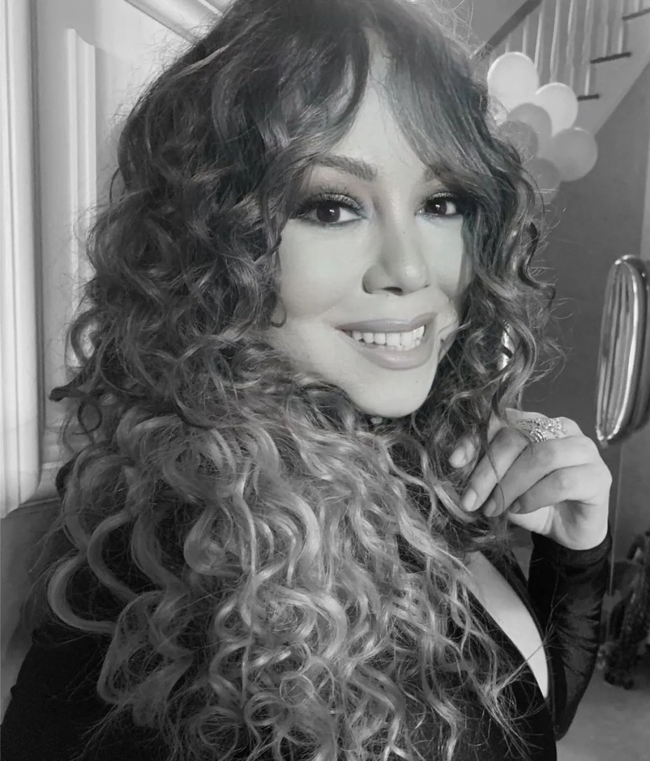 A back and white themed photo showing Mariah Carey sporting her curly waves and a huge smile.