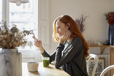 Smiling woman using phone while having breakfast