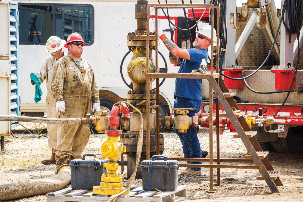 Jeff Fine (left) and Dustin Frazier prep a Quidnet Energy well for a test that involves injecting water into the rock formation below, outside of Hondo, on August 3, 2021.