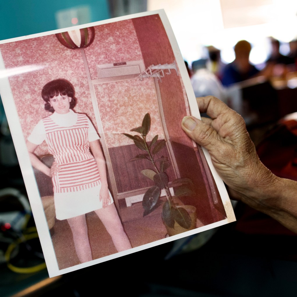 Mary Ann Hill holds a photo of herself from when she first started working at the Pig Stand on Broadway.