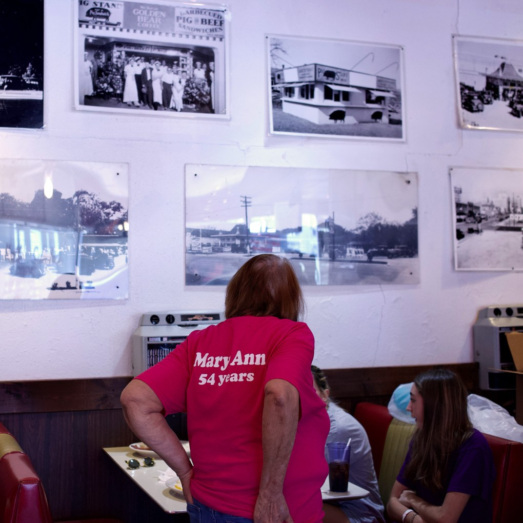 Mary Ann Hill surveys historical Pig Stand photos on the wall of the diner.