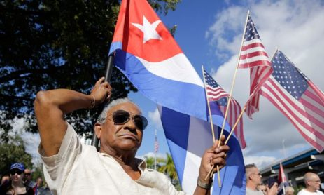 Evilio Ordonez holds Cuban and American flags during a protest against President Barack Obama's plan to normalize relations with Cuba, in the Little Havana neighborhood of Miami, Fla., on Dec. 20, 2014. (AP Photo/Lynne Sladky)