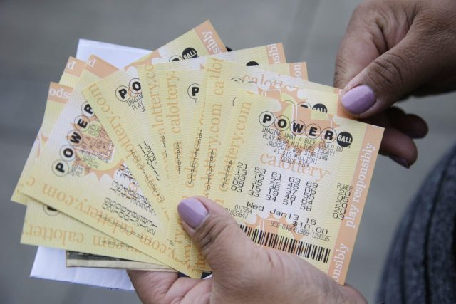 A person shows Powerball tickets she bought in San Lorenzo, Calif., on Jan. 12, 2016. The Powerball jackpot has grown to over 1 billion dollars for the next drawing on Wednesday. (AP Photo/Marcio Jose Sanchez)
