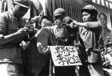 """Communist Party cadres hang a placard on the neck of a Chinese man. The words on the placard states the man's name and accuse him of being a member of the """"black class."""" (Public Domain)"""