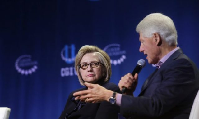 Former Secretary of State Hillary Clinton listens as former President Bill Clinton speaks during the annual Clinton Global Initiative conference at the University of Chicago on Oct. 16, 2018. (Joshua Lott/Getty Images)