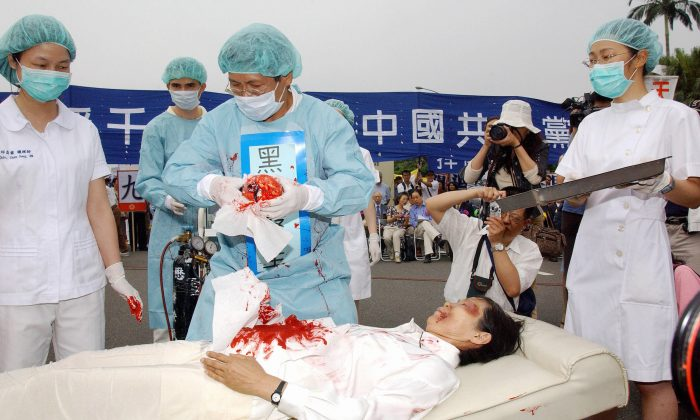 During a rally joined by thousands of Falun Gong practitioners at Taipei 23 April 2006, four demonstrators play in an action drama against what they said was the Chinese communists' killing of Falun Gong followers and harvesting of their organs in concentration camps. (Patrick Lin/AFP/Getty Images)