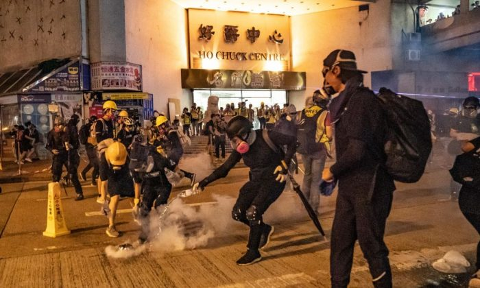 Protesters put out the tear gas as they pour water on it at Kwai Fong district, Hong Kong, on Aug. 11, 2019. (Anthony Kwan/Getty Images)