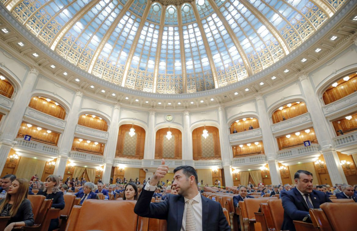A Romanian member of parliament gives a thumbs up during procedures ahead of a no confidence vote in Bucharest, Romania, Thursday, Oct. 10, 2019. (Vadim Ghirda/AP Photo)