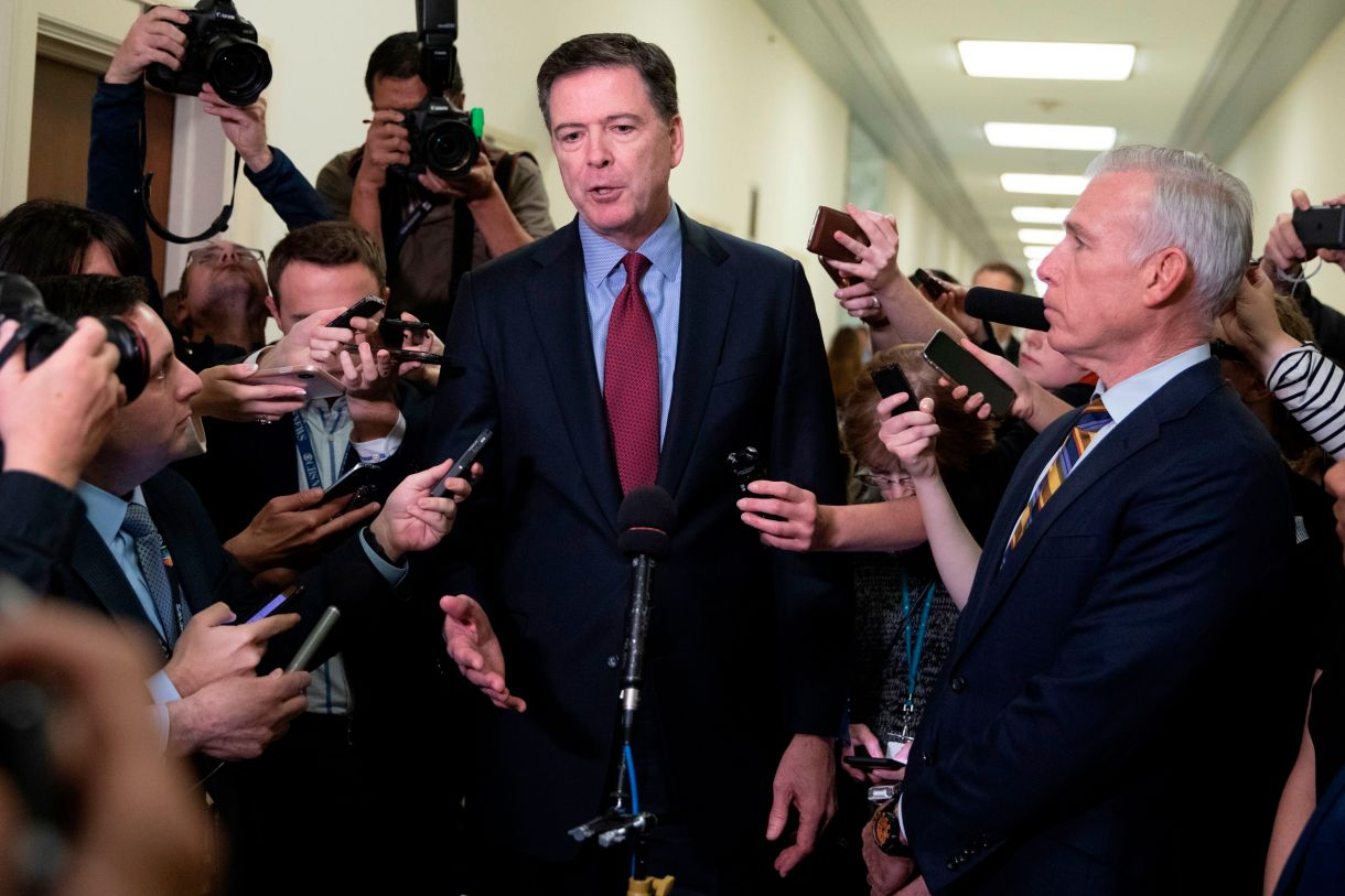 Former FBI Director James Comey (C) talks to reporters following a closed House Judiciary Committee meeting to hear his testimony, on Capitol Hill in Washington