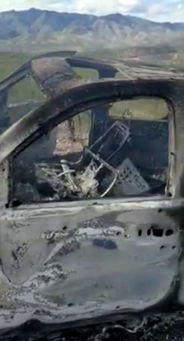 The burnt wreckage of a vehicle is seen in Bavispe