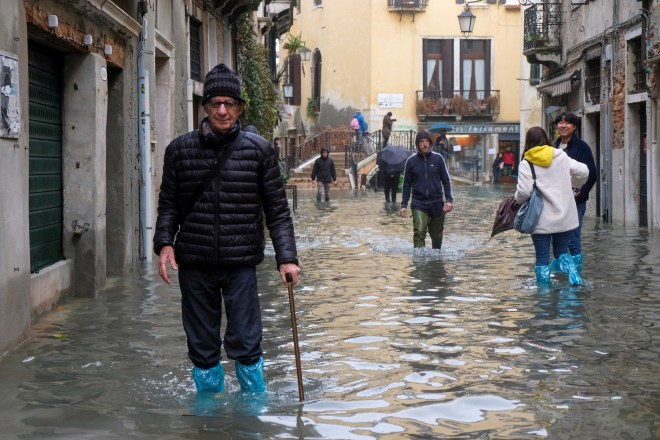 People walk outside during exceptionally high water levels in Venice
