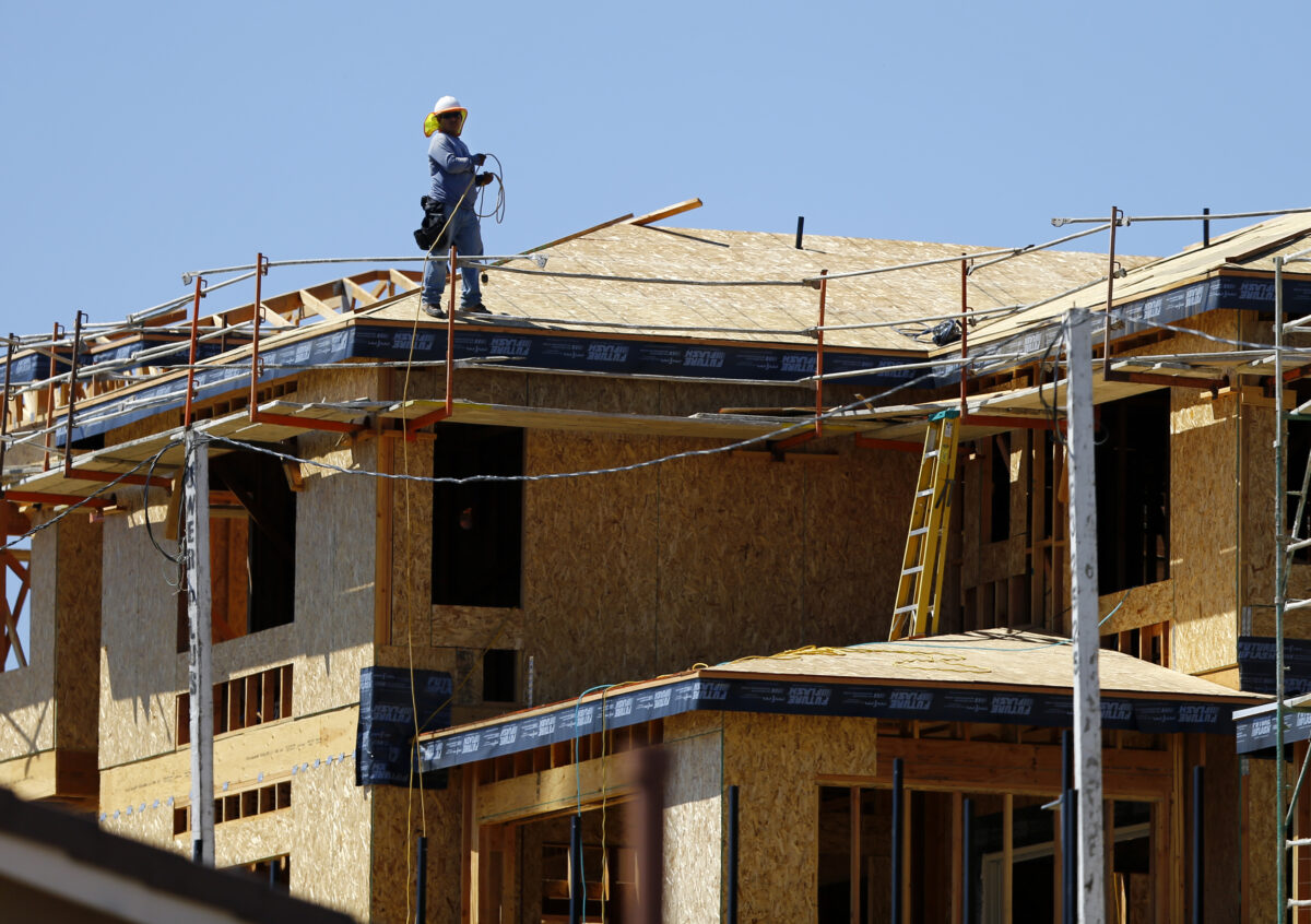 worker on roof of house