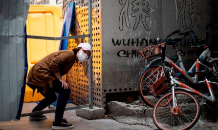 A woman wearing a face mask crosses a barricade in Wuhan China on April 7, 2020. (NOEL CELIS/AFP via Getty Images)