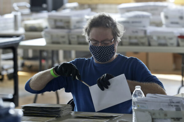Board of election worker John Carlino opens a ballot