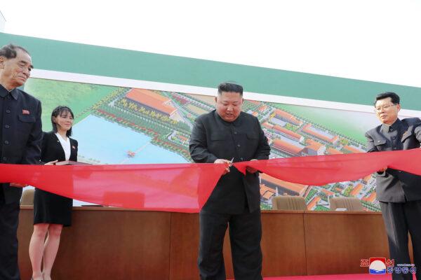 Kim Jong Un (C) cuts a tape