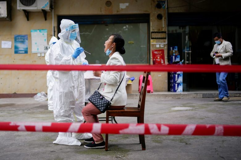 A medical worker in protective suit conducts nucleic acid testings for residents at a residential compound in Wuhan