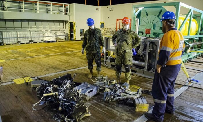 CF members and EDT Hercules personnel inspect recovered parts of the helicopter Stalker 22 during recovery operations for the aircraft in the Mediterranean Sea on May 31, 2020. (The Canadian Press/HO-Department of National Defence, Cdr Robert Watt)