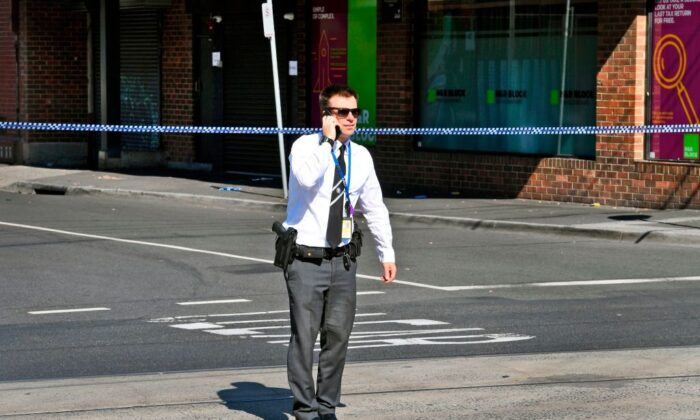 A detective speaks on the phone at the scene where a security guard was shot dead with another man fighting for his life after a drive-by shooting outside a popular Melbourne nightclub on April 14, 2019. (WILLIAM WEST/Getty Images)
