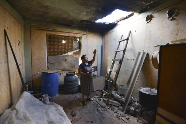 A local woman shows damage in her house-2