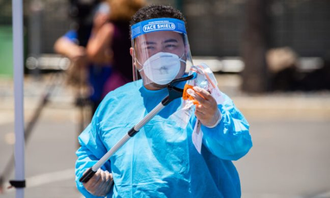 A worker handles a swab test for COVID-19 at a testing site at the Anaheim Convention Center, in Anaheim, Calif., on July 15, 2020. (John Fredricks/The Epoch Times)