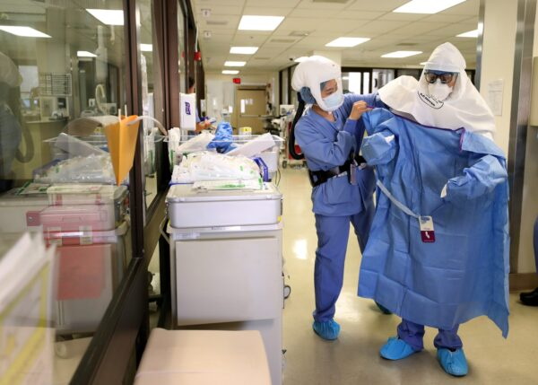 A nurse helps a doctor put on his PPE