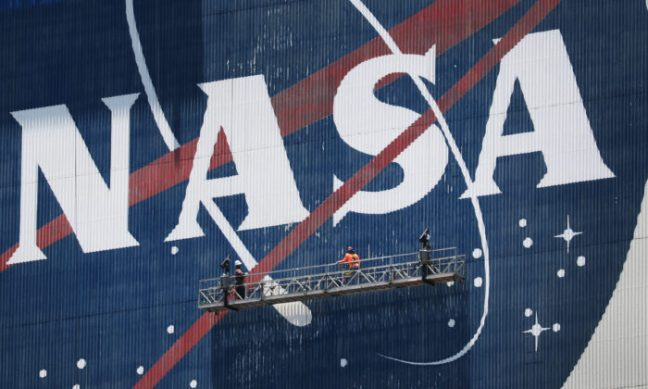 Workers freshen up the paint on the NASA logo on the Vehicle Assembly Building before the arrival of NASA astronauts Bob Behnken and Doug Hurley at the Kennedy Space Center in Cape Canaveral, Fla., on May 20, 2020. (Joe Raedle/Getty Images)
