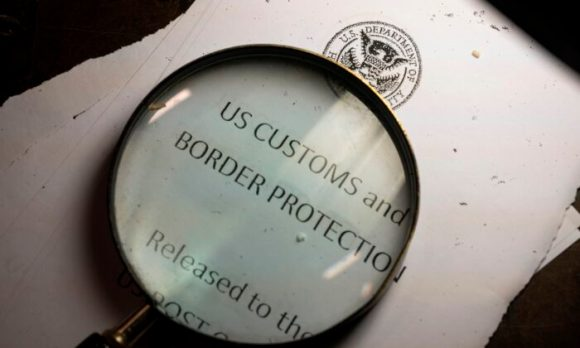 A magnifying glass is seen next to a logo of the Customs and Border Protection, Trade and Cargo Division at John F. Kennedy Airport's US Postal Service facility in New York on June 24, 2019. (Johannes Eisele/AFP via Getty Images)