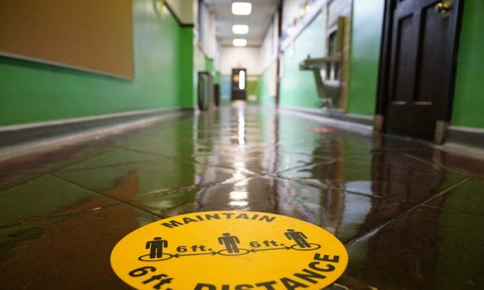A social distancing reminder is posted on a hallway floor of Nebinger Elementary School in Philadelphia, Pa., on March 19, 2021. (Matt Rourke/AP Photo)