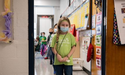 Masked students wait in a socially distanced single file line before heading to the cafeteria at Medora Elementary School in Louisville, Ky., on March 17, 2021. (Jon Cherry/Getty Images)