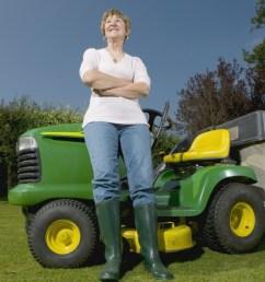 woman standing next to a riding lawn mower  [ 1200 x 799 Pixel ]