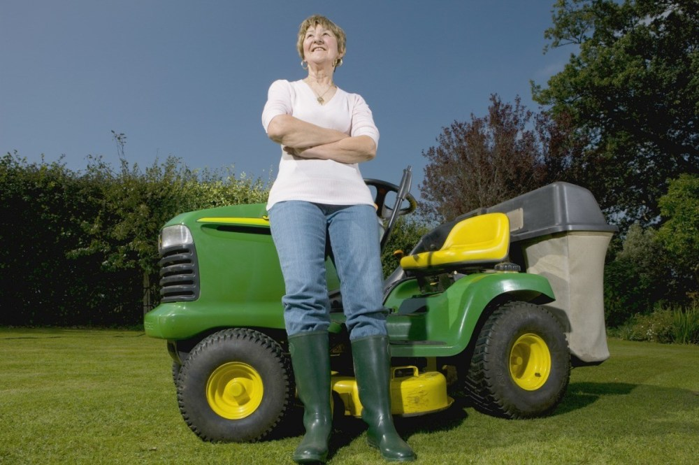 medium resolution of woman standing next to a riding lawn mower