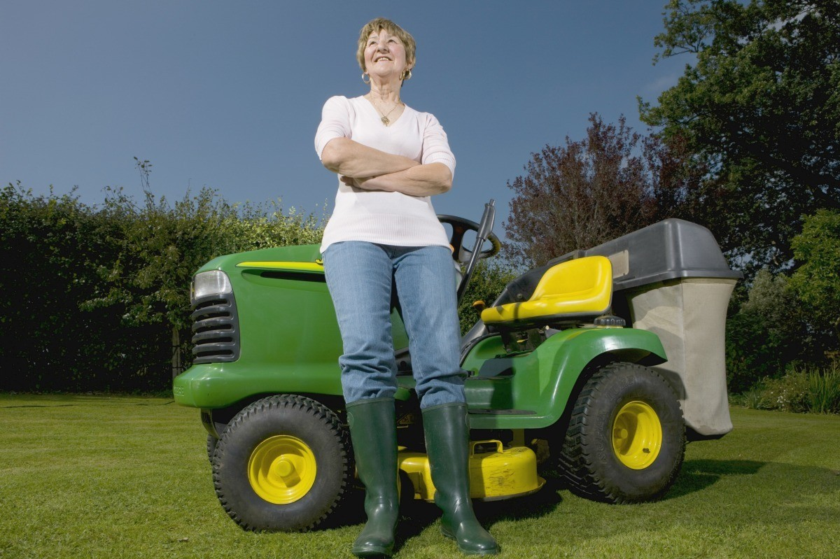hight resolution of woman standing next to a riding lawn mower