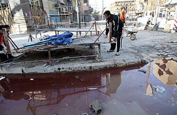 Iraqis remove broken street shop stalls from the site of a bomb attack in Baghdad's Karrada neighborhood.