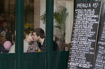 23 Jan 2006, Paris, France --- A couple in a Left Bank restaurant kiss. --- Image by © Philip Gould/Corbis