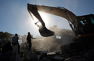 Residents watch as a bulldozer razes a destroyed building.