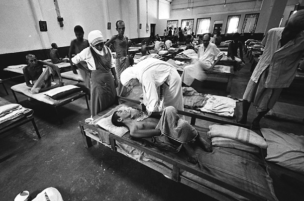 Mother Teresa comforts a patient at a hospital. At the time of her death in 1997, her charity operated 610 missions in 123 countries which included hospices and homes for orphans, HIV/AIDS patients and people with leprosy.